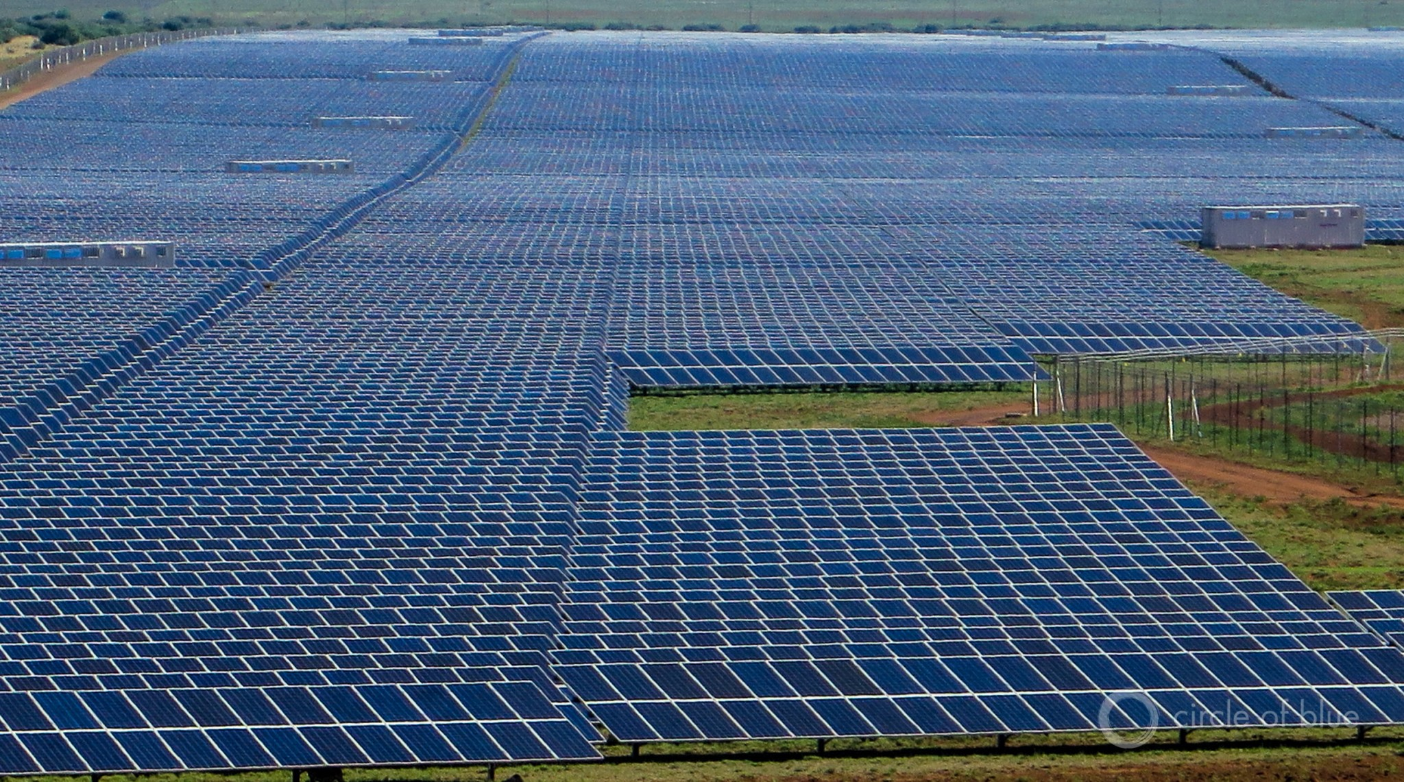 The expanse of electricity generating panels at the Jasper solar photovoltaic power station in the Northern Cape reflects the sun and the sky, and is so large that from a distance it looks like shimmering blue lake. Photo © Keith Schneider / Circle of Blue