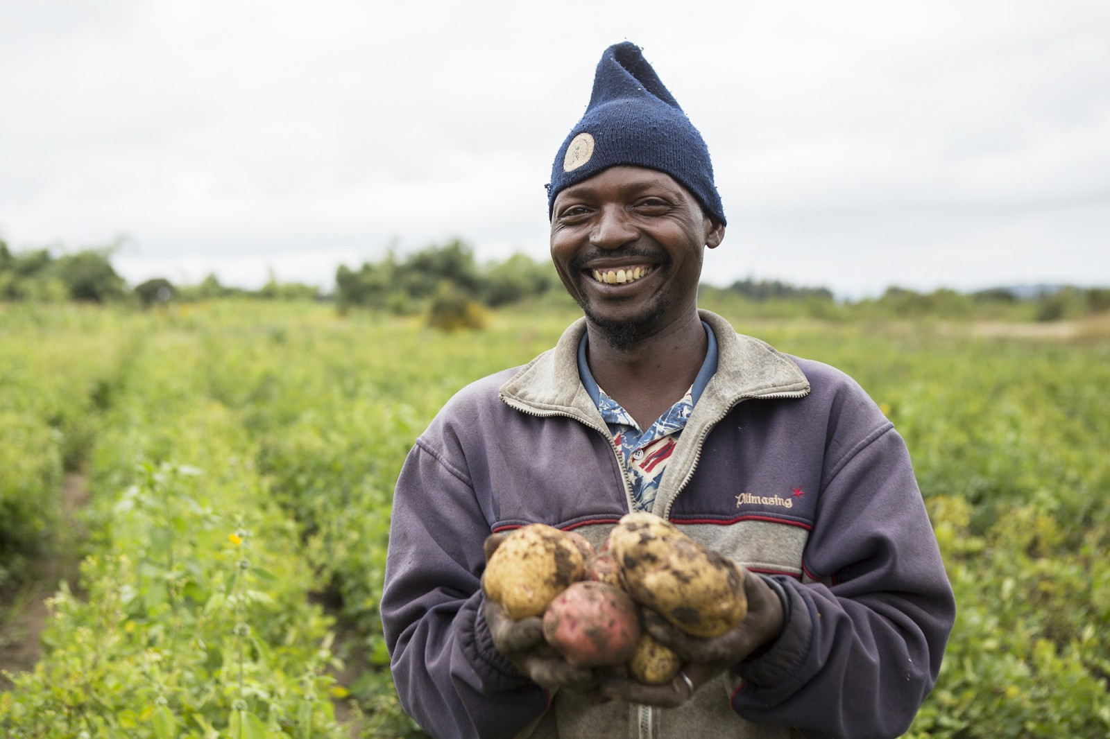 """A farmer shows off potatoes he has grown near Iringa, Tanzania, which lies within the Southern Agricultural Growth Corridor. The project's stated objective is to """"foster inclusive, commercially successful agribusinesses."""" Photo courtesy USAID/Tanzania via Flickr Creative Commons"""